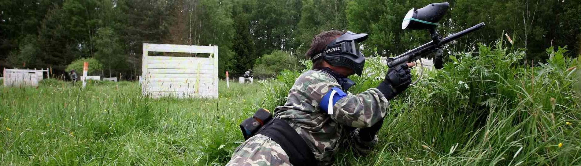 buck playing paintball hiding in grass