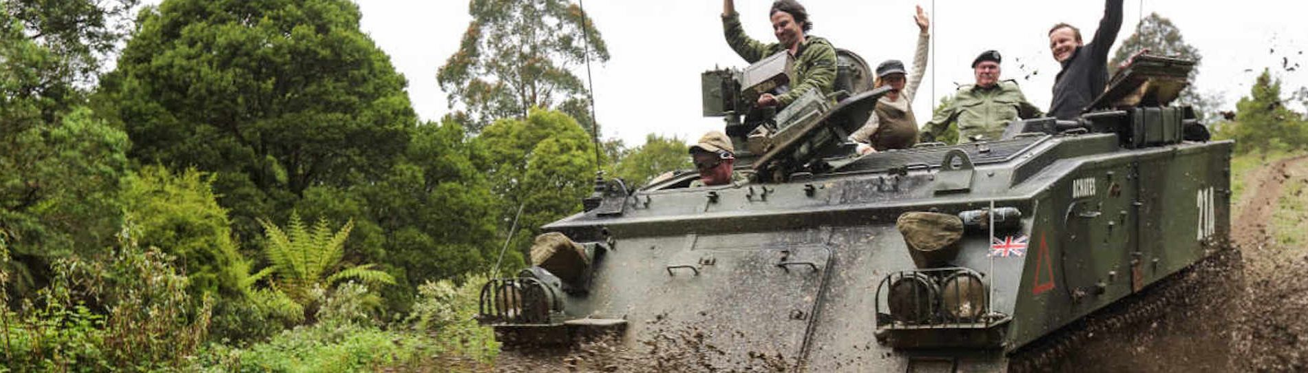 bucks riding in army tank as mud splashes