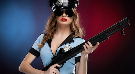 female police officer wearing black sunglasses and red lipstick holding large gun