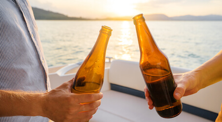 two bucks cheers beers on back of boat charter