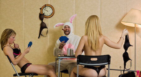 bucks in bunny outfit with two topless waitresses playing poker