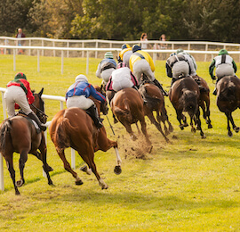 horses racing around the bend of race track