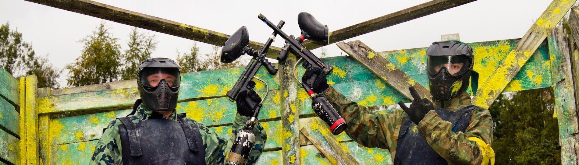 two bucks crossing paintball guns posing