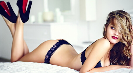 blonde women in black lingerie and black and red heels lying on white bed
