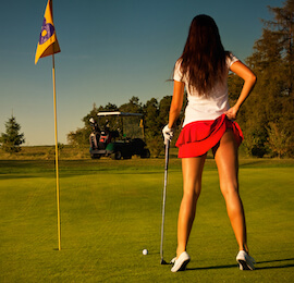 cheeky golf bunny in red skirt holding golf club on the green