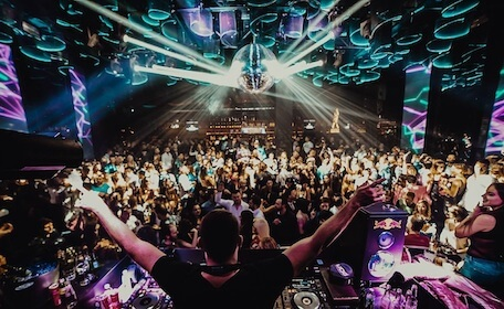 large crowd partying at nightclub with DJ