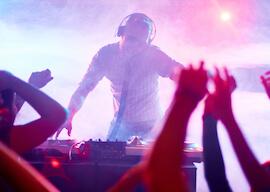 DJ playing at nightclub while crowd dances