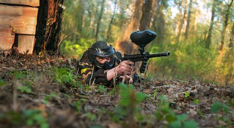buck lying on ground shooting paintball gun