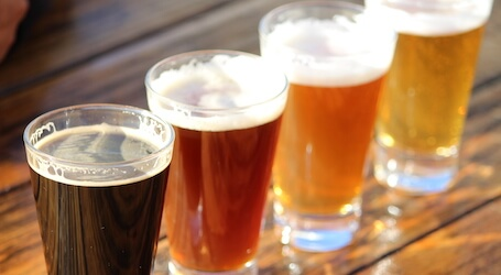 four beers lined up at bar