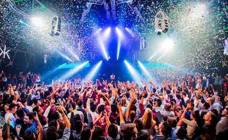 large crowd dancing at nightclub to dj with falling confetti and flashing lights