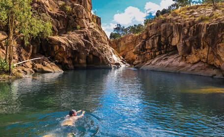 man swimming in blue Darwin lake with rocks surronding