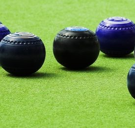 6 lawn bowls sitting on grass