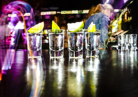 four shots of alcohol on nightclub bar with lemon on top