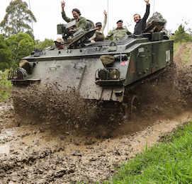 bucks riding in army tank as mud splashes