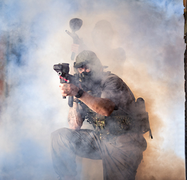 man playing paintball shooting gun in smoke