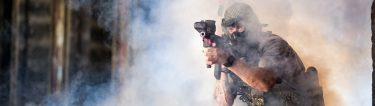 army man shooting paintball gun surrounded by smoke