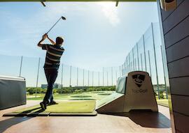 buck swinging club at top golfing range