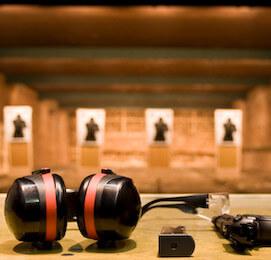 ear muffs, hand gun ammo and gun on bench