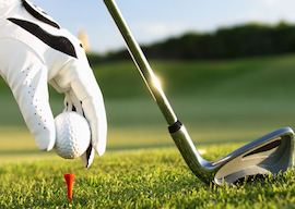 buck putting golf ball on tee with club