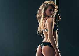 stunning stripper in black lingerie holding stripper pole
