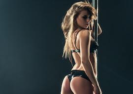 stunning stripper in black lingerie holding stripper pole
