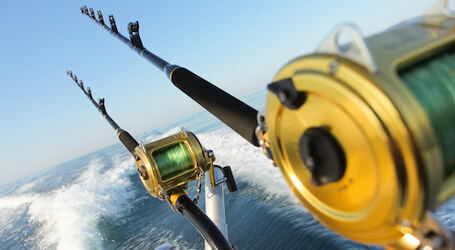 two deep sea fishing rods off back of boat