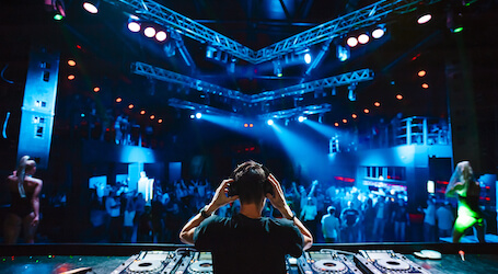 dj in nightclub with decks and led lights