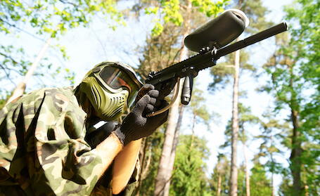 buck in paintball gear shooting gun