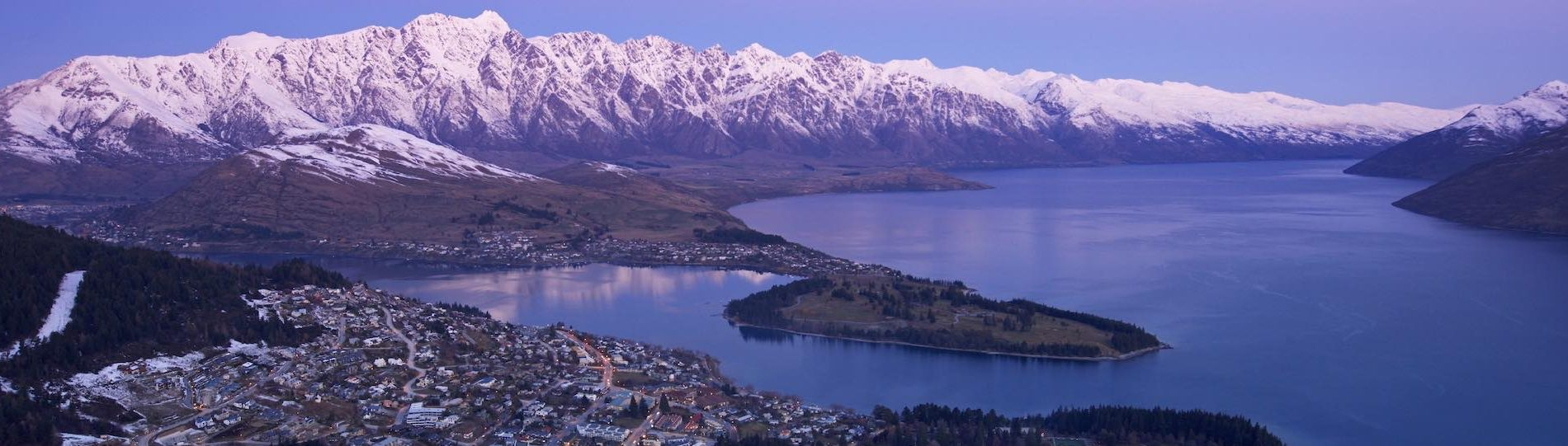 city buildings, river and snowy mountains in queenstown