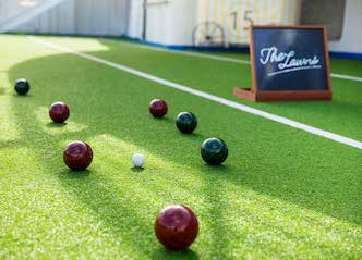 group of bucks playing barefoot bowls perth