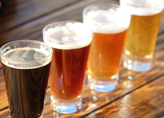 four beers lined up on wooden table