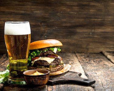 big burger and beer on wooden palate