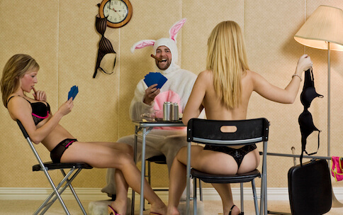 buck in bunny costume playing poker with two waitressess