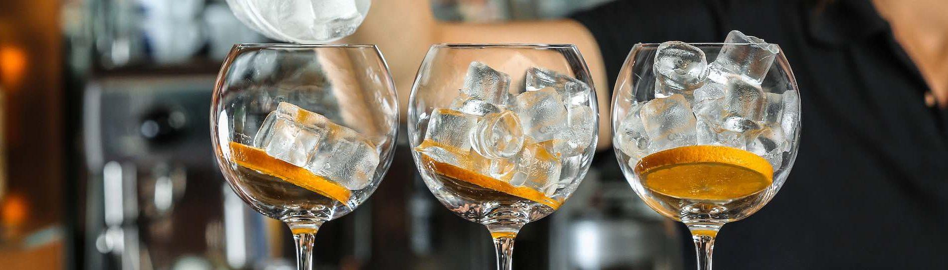 bartender making three drinks at bar