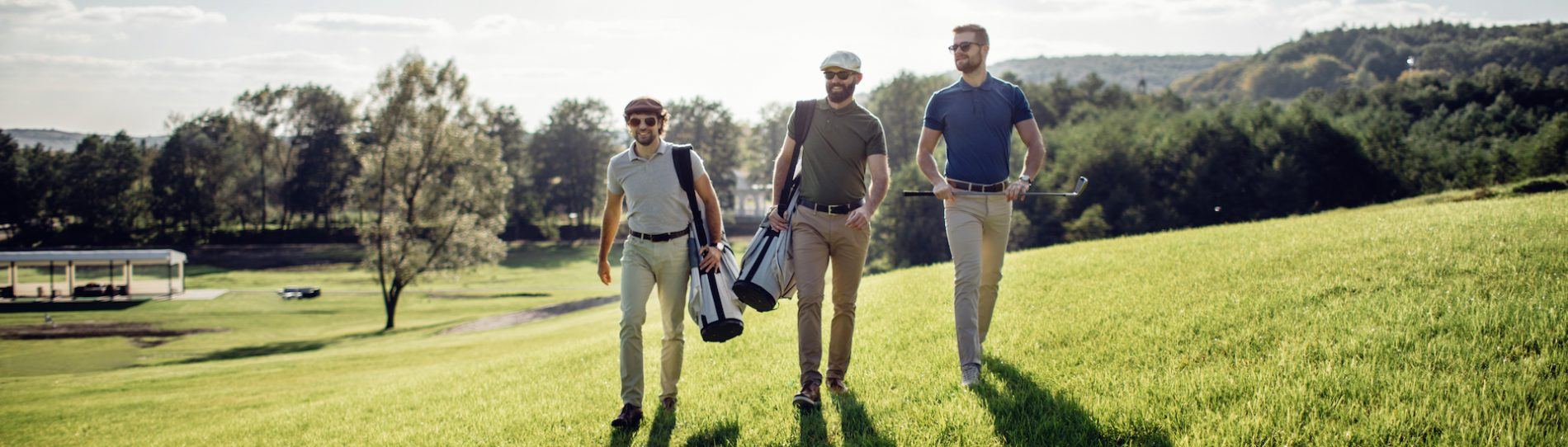 bucks walking on golf course with clubs