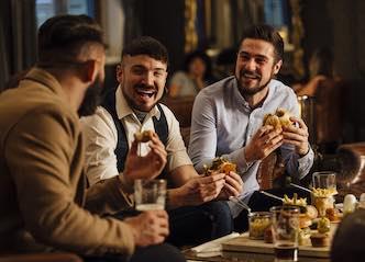 bucks group eating burgers at bar