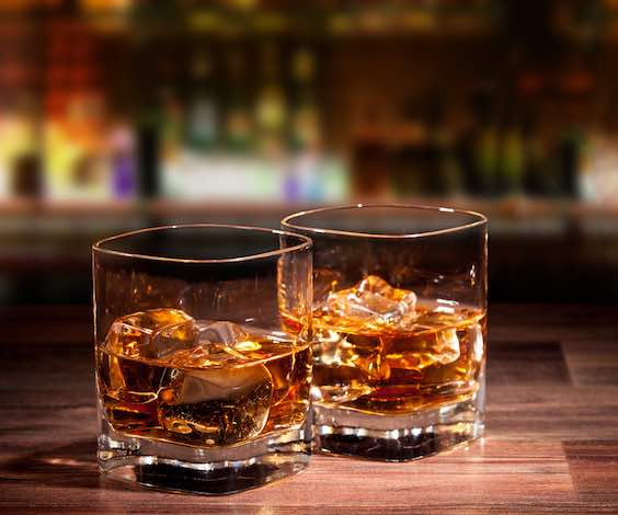 two glasses of whiskey on bar