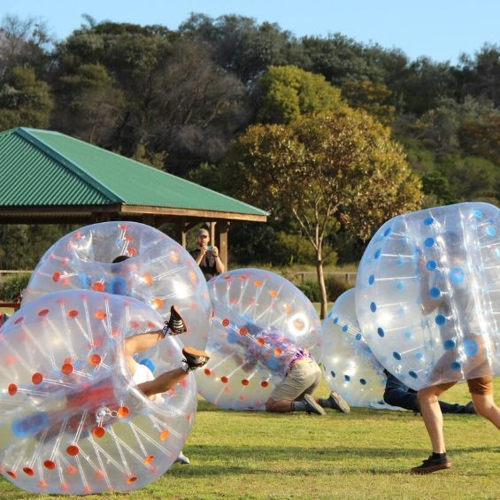 guys playing outside with bubble soccer